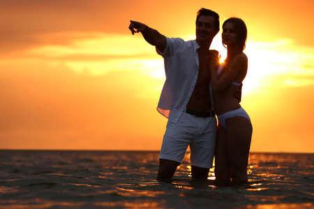 Feliz pareja joven pasar tiempo juntos en la playa al atardecer