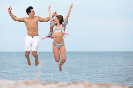 Happy young couple jumping together on sea beach. Space for text