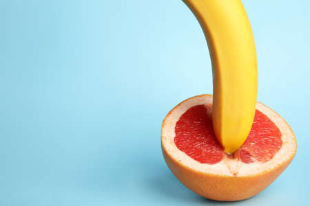 Fresh grapefruit and banana on blue background, space for text. Sex concept