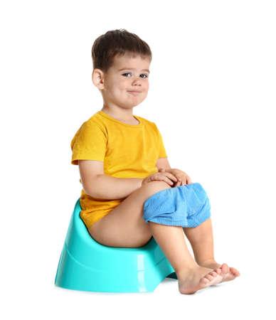 Portret van kleine jongen zittend op potje tegen witte achtergrond Stockfoto