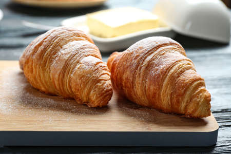 Wooden board with tasty croissants on table, closeup. French pastry