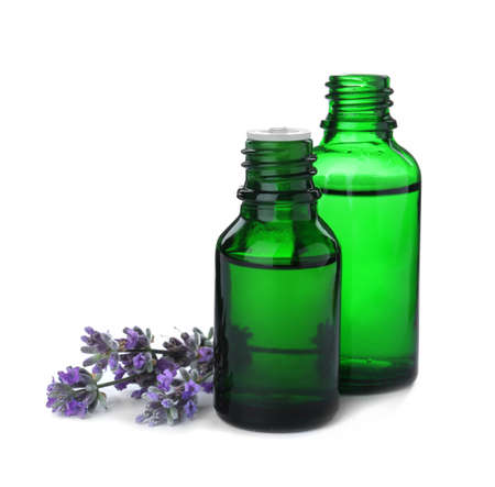 Bottles of essential oil and lavender flowers isolated on white