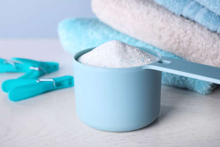 Measuring spoon of laundry powder near towels and clothespins on table