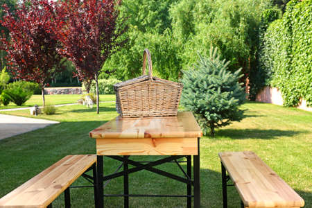 Picnic basket on wooden table in green park Stockfoto - 128582640