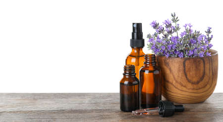 Bottles of essential oil and bowl with lavender flowers on wooden table against white background