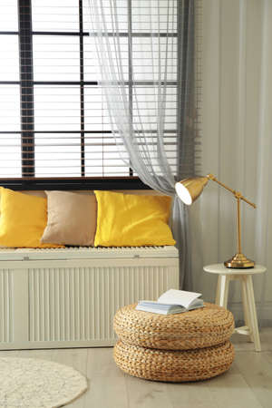 Wooden chest with pillows near window in room. Interior design