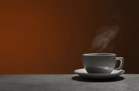 Ceramic cup of hot fresh tea on stone table against brown background, space for text Stock Photo