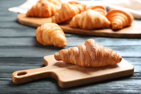 Fresh croissants on dark wooden table. French pastry