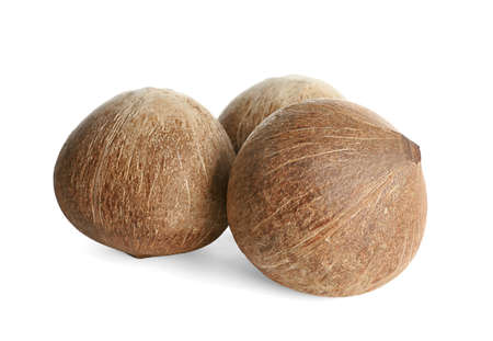 Ripe whole brown coconuts on white background Imagens
