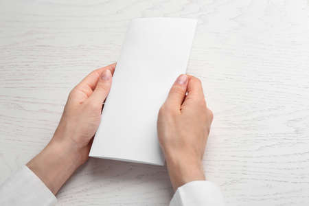 Young woman holding blank brochure at white wooden table, closeup. Mock up for design