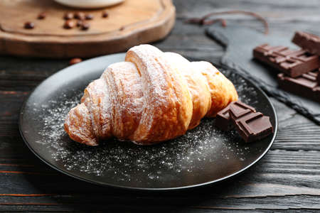 Plate of tasty croissant with powdered sugar and chocolate on dark wooden table. French pastry