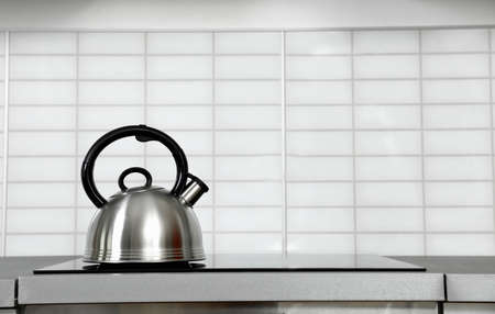 Modern kettle with whistle on stove in kitchen, space for text Banco de Imagens