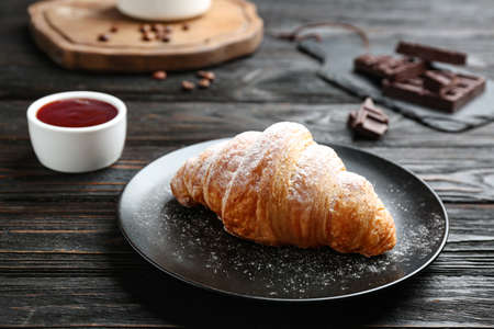 Plate with tasty croissant and powdered sugar on dark wooden table. French pastry