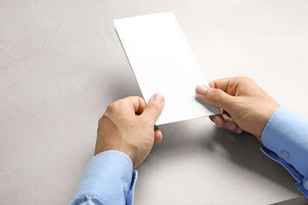 Young man holding blank brochure at grey table, closeup. Mock up for design