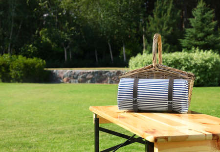 Picnic basket with blanket on wooden table in green park Stockfoto - 128583636