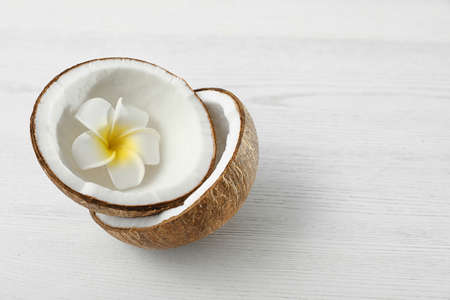 Halves of coconut and flower on white wooden background. Space for text Imagens