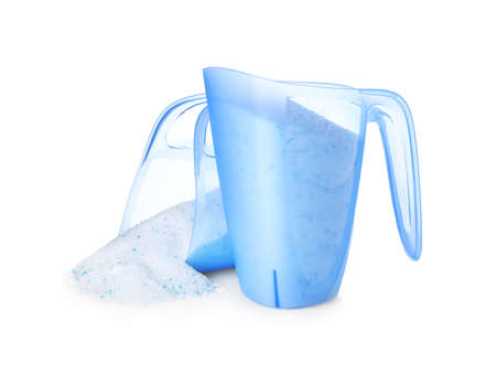 Measuring cups with laundry detergent on white background
