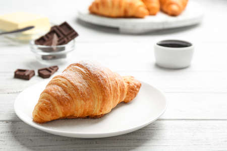 Plate with tasty croissant on white wooden table. French pastry