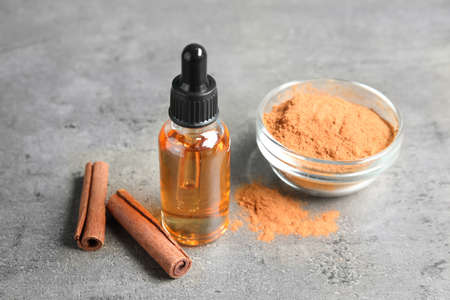 Bottle of essential oil, cinnamon sticks and powder on grey table Stock Photo