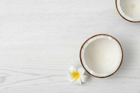 Halves of coconut and flower on white wooden background, top view. Space for text