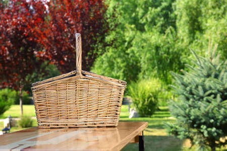 Picnic basket on wooden table in green park Stockfoto - 128584436