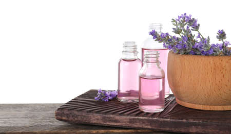 Bottles of lavender essential oil and bowl with lavender flowers on wooden table against white background 写真素材