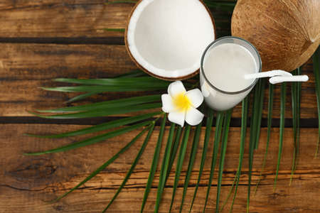 Composition with glass of coconut water on wooden background, top view Imagens