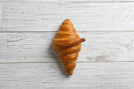 Tasty croissant on white wooden background, top view. French pastry