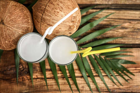Flat lay composition with glasses of coconut water on wooden background