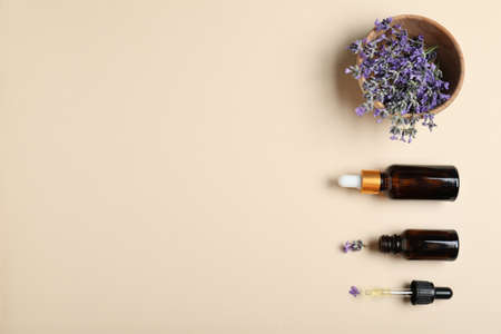 Bottles of essential oil and lavender flowers in bowl on beige background, flat lay. Space for text