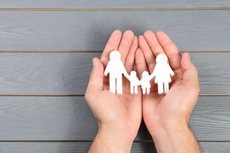 Joven sosteniendo la figura familiar en sus manos contra el fondo de madera gris, vista superior. Espacio para texto Foto de archivo