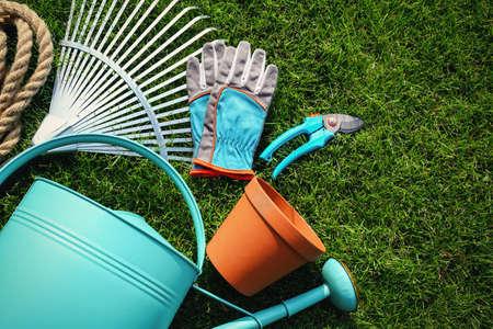 Set of gardening tools on green grass, flat lay