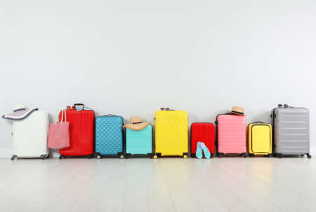 Trendy composition with colorful suitcases near light wall. Space for text
