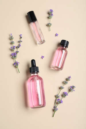 Bottles of essential oil and lavender flowers on beige background, flat lay