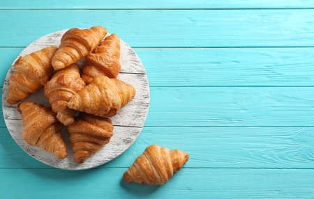 Board with tasty croissants and space for text on light blue background, flat lay. French pastry