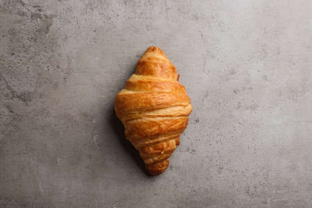 Tasty croissant on grey background, top view. French pastry
