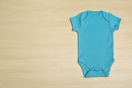 Cute baby clothes  on wooden background, top view. Space for text