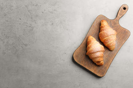 Wooden board with tasty croissants and space for text on grey background, top view. French pastry