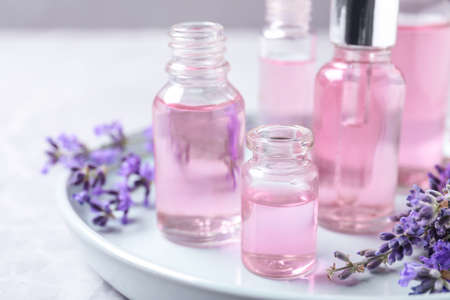 Tray with bottles of lavender essential oil and flowers on table 写真素材
