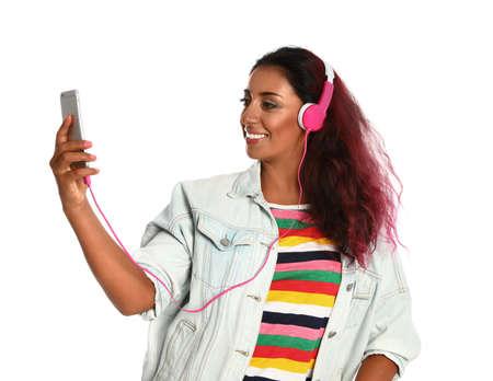 Beautiful Hispanic woman taking selfie on white background