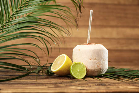 Open fresh coconut and citrus fruits on wooden table