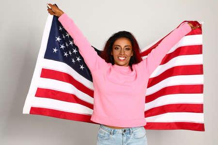 Hermosa mujer hispana con bandera estadounidense sobre fondo claro Foto de archivo