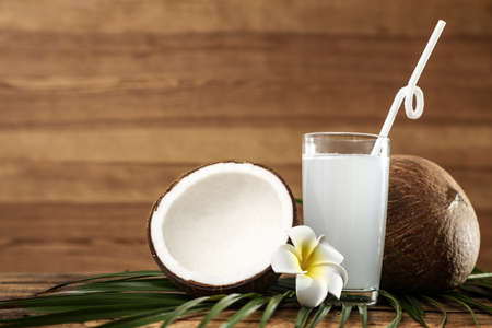 Composition with glass of coconut water on wooden background