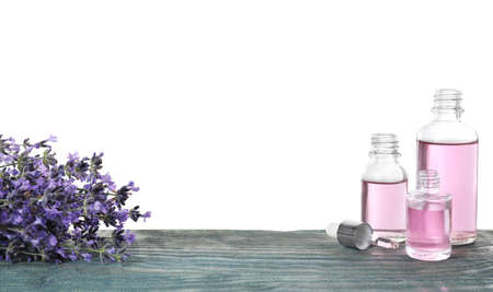 Bottles of essential oil and lavender flowers on blue wooden table against white background 写真素材