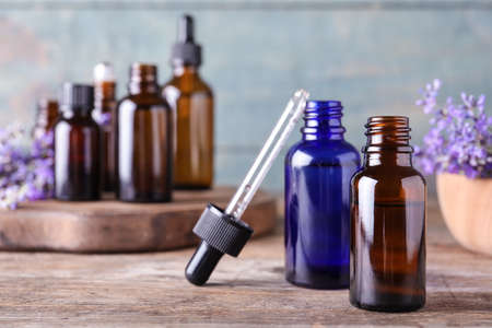 Bottles of lavender essential oil and flowers on wooden table against blue background 写真素材