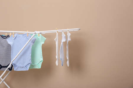 Different cute baby clothes  hanging on clothes line against beige background, space for text. Laundry day Banco de Imagens