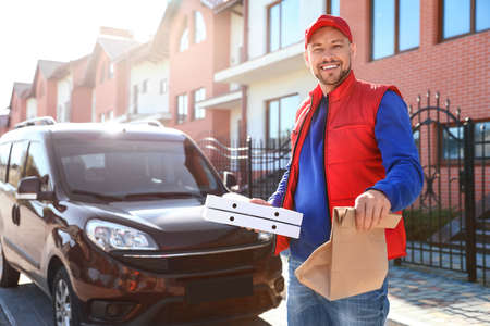 Male courier delivering food in city on sunny day