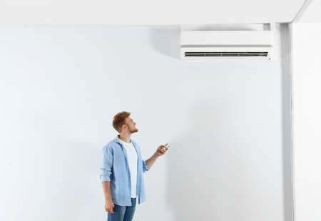 Young man operating air conditioner with remote control indoors. Space for text Stock Photo - 128758414