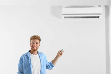 Young man operating air conditioner with remote control indoors. Space for text Stock Photo