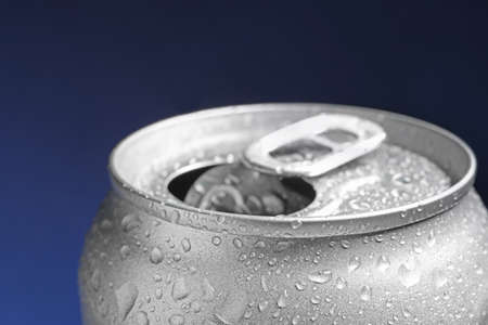Wet open can on blue background, closeup